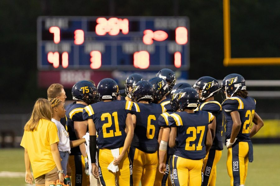 The football team huddles at the home game on 9/13/2019